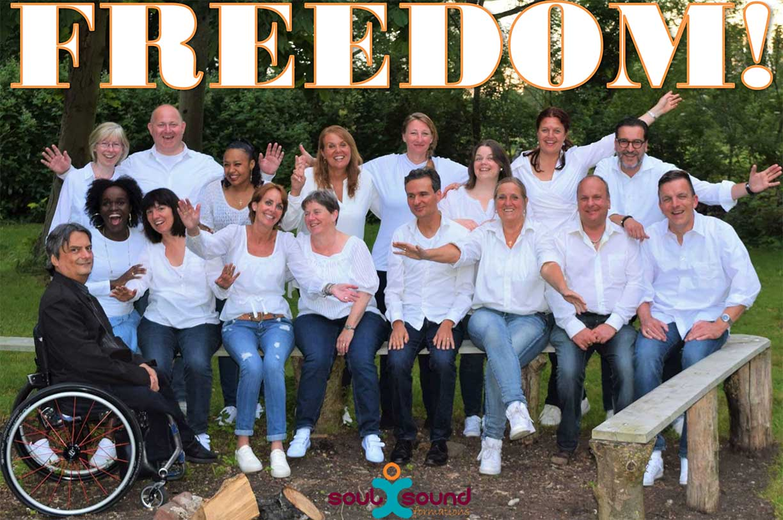 Tekst in de foro: Freedom! Beeld: het koor zittend in een bosrijke omgeving.